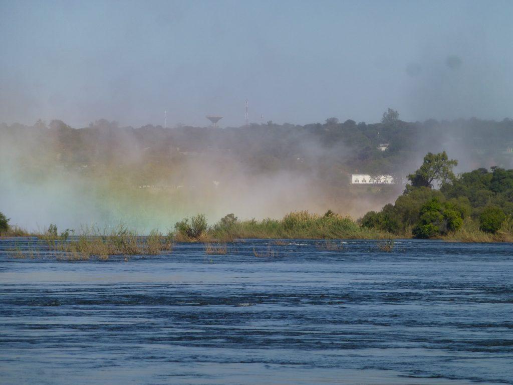 Blick vom Ufer des Sambesi auf der sambianischen Seite auf die Victoria Wasserfälle